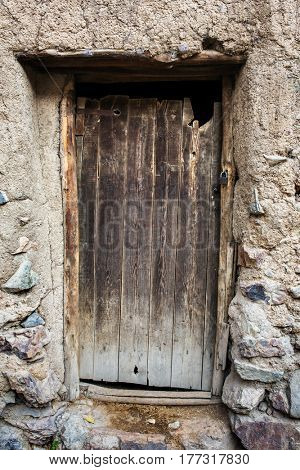 Old wooden door in stone house