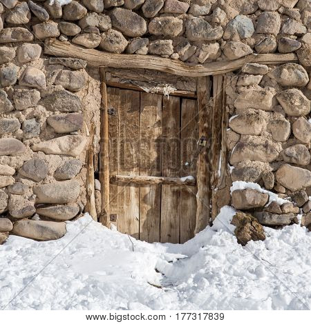Old wooden door in stone house in Kandovan vilage near Tabriz, Iran