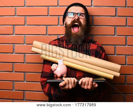 Bearded man long beard. Brutal caucasian happy unshaven hipster holding craft paper rolls piggy bank on laptop in checkered shirt with hat and glasses on brown brick wall studio background