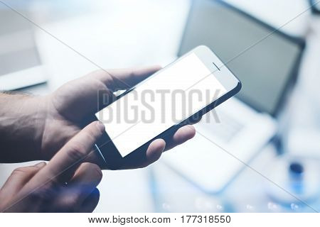 Closeup view of man hands holding modern mobile phone with white empty screen and pointing finger to home button.Horizontal mockup, blurred background, visual effects