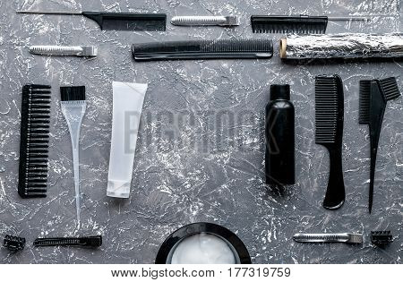 hair dye in bottle with brush in hairdress concept on gray table background top view mock up