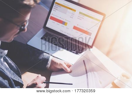 Adult elegant businessman in eyeglasses working at sunny office on laptop while sitting at wooden table.Coworker analyze document in his hands.Graphs and diagramm on notebook screen Blurred background