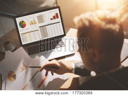 Adult banking analyst in eyeglasses working at sunny office on laptop while sitting at wooden table.Businessman analyze document in his hands.Graphs and diagramm on notebook screen.Blurred background