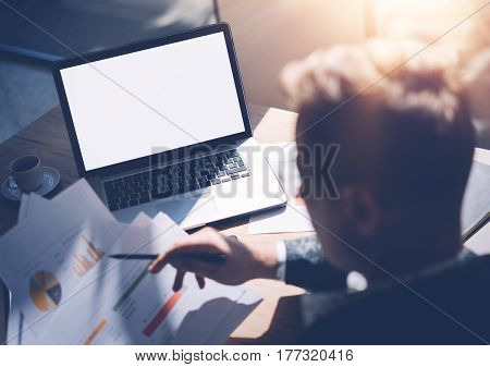 Adult banking analyst in eyeglasses working at sunny office on laptop while sitting at wooden table.Businessman analyze document in his hands.Graphs and diagramm on notebook screen.Horizontal mockup