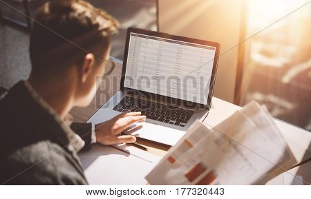 Young banking finance analyst in eyeglasses working at sunny office on laptop while sitting at wooden table.Businessman analyze stock reports on notebook screen.Blurred background, horizontal