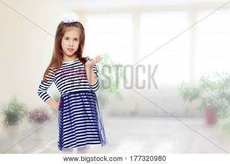 Beautiful little girl long hair and white bow on her head , in a summer dress in stripes.She pointed a hand to the side.In the room with the big bright window in the wall.