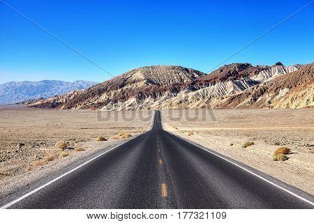 Desert Road Towards Mountain Range At Death Valley.