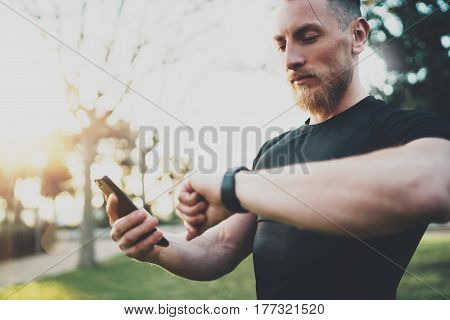 Muscular bearded athlete checking burned calories on smartphone application and smart watch after good workout session on city park.Blurred background