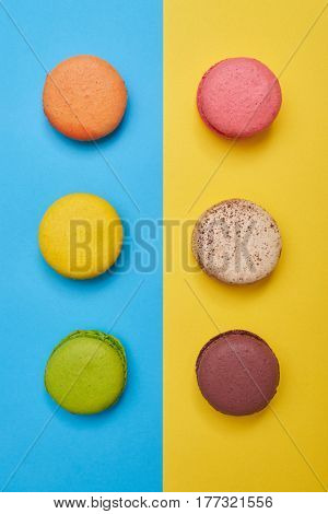 Top view of bright macaroons arranged in two line over blue flatlay. Two lines of homemade confection