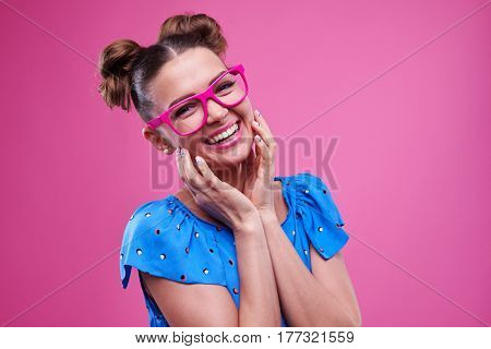 Close-up of joyous girl with two buns wearing pink glasses isolated over pink background. Wearing lovely dotted outfit
