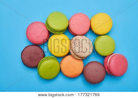 Colorful heap of macaroons isolated over blue flatlay. Assorted colorful french cookies macaroons