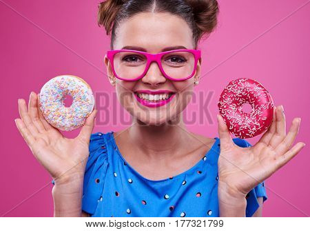 Portrait shot of stylish girl in pink glasses holds a tasty doughnuts and smiling broadly. Pink lipped female with two tasty