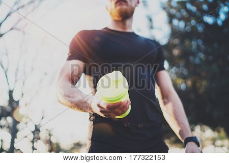 Workout fitness concept.Muscular bearded athlete with protein milk shake cocktail after hard workout session on city park in the sunny morning.Blurred background
