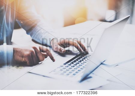 Man working at the wooden table at modern loft office.Man sitting at workplace and typing on laptop keyboard.Blurred background.Horizontal, visual effects