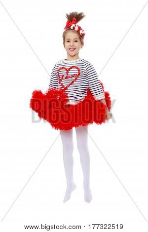 Little girl in a red skirt and bow on her head.She jumps waving her arms.Isolated on white background.
