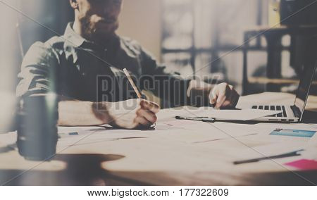 Young bearded coworker working in modern loft office. Man using contemporary notebook while sitting at the wooden table and making notes. Panoramic windows on the blurred background.Color mask