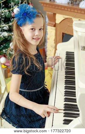 Beautiful, elegant little girl holding hands on the keys of a white Grand piano. Girl playing at the Christmas concert in the music school.
