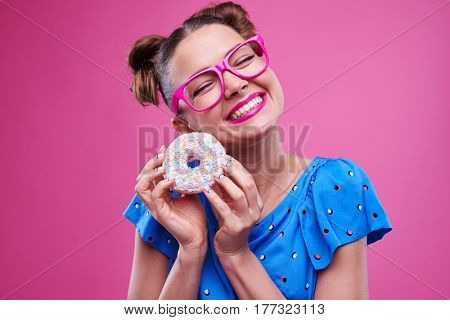 Close-up of exhilarated smiling woman with sprinkled donut. Elated woman in bright outfit over pink background
