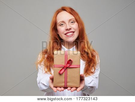 Close-up of smiling teenager giving gift box. Wrapped container with a present. The concept of holidays, celebrations