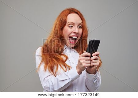 Close-up of red hair enthusiastic teen with a mobile phone in hands. Girl posing isolated over background in the studio