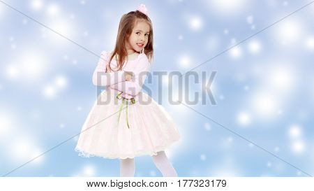 Dressy little girl long blonde hair, beautiful pink dress and a rose in her hair.One folded his arms.Blue Christmas festive background with white snowflakes.