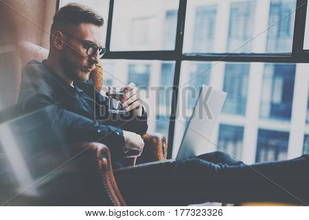 Pensive bearded businessman working at the modern loft office.Man sitting in vintage chair, holding in hands glass of water, using contemporary notebook.Panoramic window on blurred background Horizontal