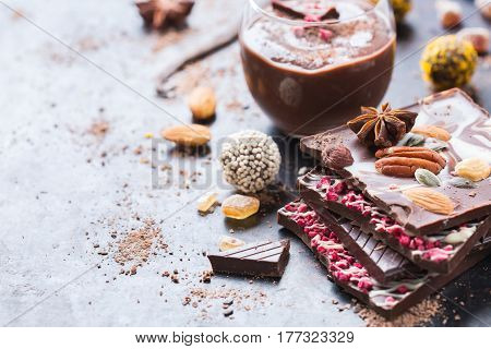 Sweet and treat, junk unhealthy food. Assortment of chocolate bar and praline truffle and mousse with spices and nuts on black moody grunge table. Copy space background