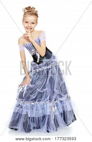 Slender little girl , with beautiful hair on his head, elegant long Princess dress.Girl holding finger at her lips. The gesture quiet.Isolated on white background.