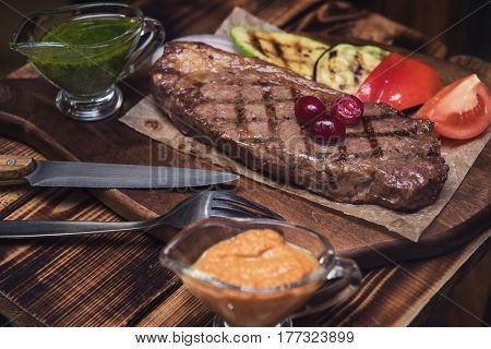 grilled beef steak with sauce and vegetables