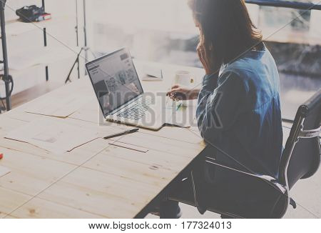 Student work process concept. Photo of young woman working on university project with laptop computer at the wooden table.Blurred background, film effect. Horizontal.