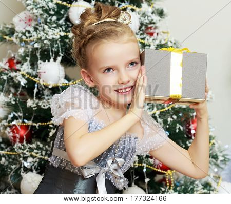 Beautiful little girl in a dress of Princess around the Christmas tree.She enjoys the gift which keeps in the hands. Close-up.