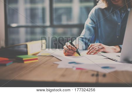 Working process at modern office.Account manager working at the wooden table with paper documents.Blurred background.
