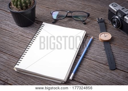 Notebook Camera cactus wristwatch and pencil on wood background.
