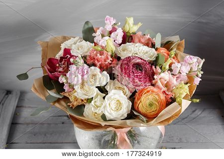 Bouquet of roses and Other colors flowers on wooden background, copy space