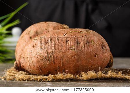 Sweet potatoes on a rustic wooden board.