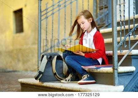 Adorable Little Schoolgirl Studying Outdoors On Bright Autumn Day. Young Student Doing Her Homework.