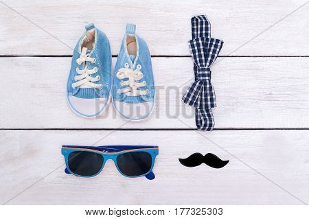 baby boy accessories on wooden background. flat lay