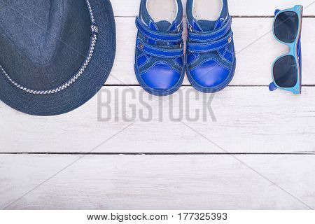 Children's accessories blue for summer: sunglasses; hat; boots. flat lay