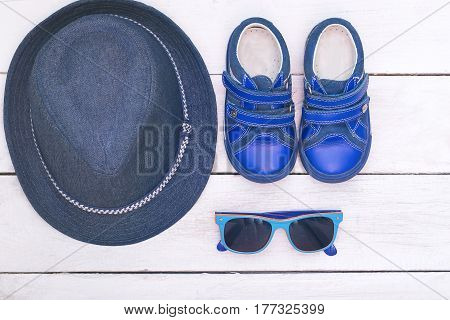 Children's accessories for the summer: sunglasses; hat; boots blue. Flat lay
