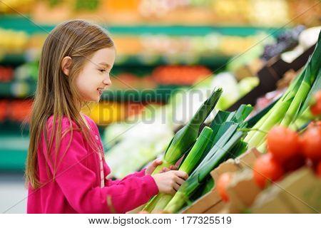 Little Girl Choosing Fresh Leek In A Food Store