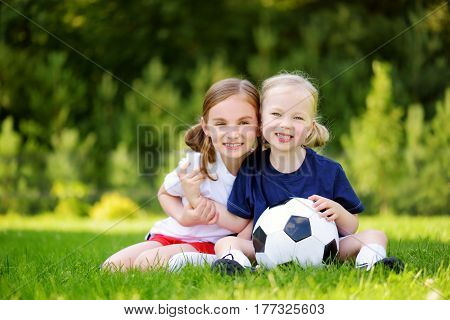 Two Cute Little Sisters Having Fun Playing A Soccer Game On Sunny Summer Day. Sport Activities For C