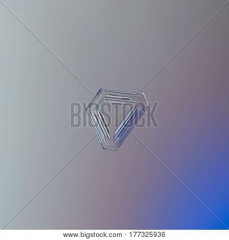 Macro photo of real snowflake: rare triangular snow crystal with glossy, relief surface and simple pattern of straight lines and ridges inside. Snowflake glittering on bright gray - pink - blue gradient background.