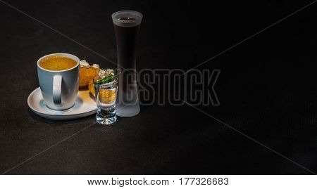 Black Coffee In White Cup, With Croissants On Saucer, Liqueur And Vodka, Peppers