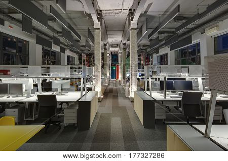 Glowing office in a loft style with gray walls, concrete columns and a carpet. There are many workplaces with computers and metal reticulated shelves and lockers, shelves with books and red ladders.