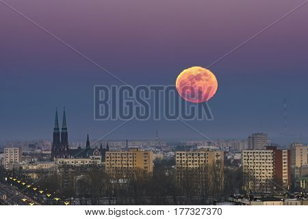 Rising moon over Warsaw city in winter time