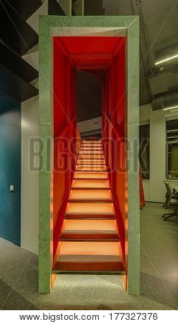 Futuristic green-red stairway with a backlight in the office in a loft style. There is a gray carpet on the floor. Closeup Vertical.