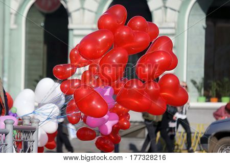 balloons in the shape of a heart fluttering from the wind in the city
