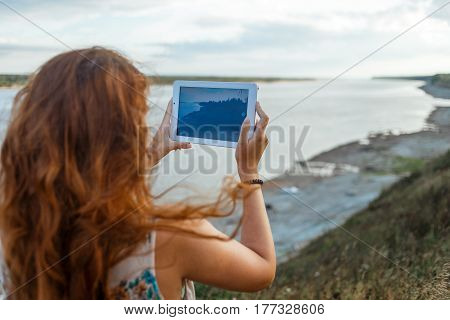 Back view of a young woman wanderer is making photo with portable tablet camera during her vacations in village meadows with great river.