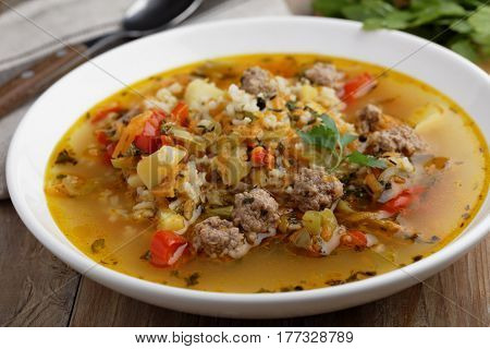 Meatball soup with rice and vegetables on a rustic table