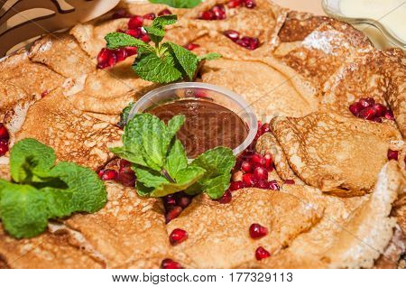 Pancakes with jam, decorated with pomegranate seeds and leaves of fragrant mint during the celebration Russian Shrovetide (pancake week)